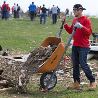 An NIU football player helps with the recovery in Fairdale.