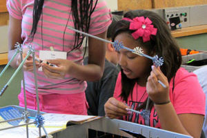 A camper in Engineering Amusement designs and constructs a model roller coaster.