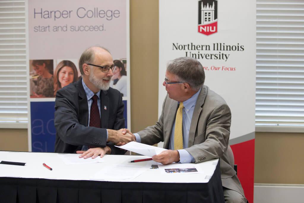 NIU President Doug Baker and Harper College President Ken Ender sign the reverse transfer agreement.