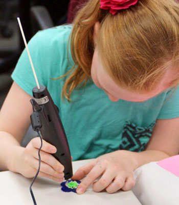 A participant in a STEM Divas Saturday class works on her original creation using a 3Doodler, a hand-held 3-D printing device.