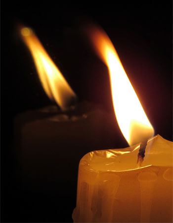 A photo of a candle with its reflection