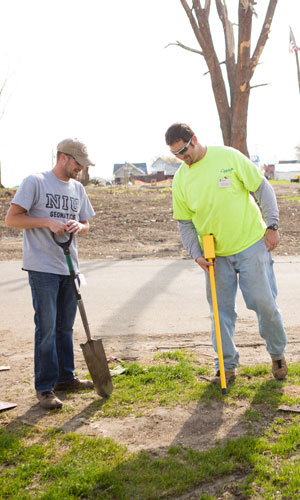 Instructor Kory Allred (right) and NIU student Jeremy Daehne search for buried property corner markers to re-survey parcels of land in Fairdale.