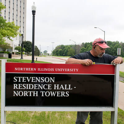 New campus signage is installed outside the North Towers of Stevenson Residence Hall.