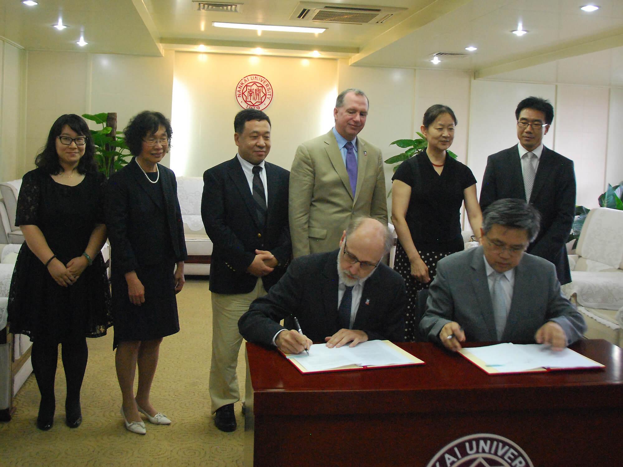 NIU President Doug Baker and Nankai President Gong Ke sign the NNIC agreement, joined by (L to R) Joanna Shen, Pauline Wang, Liu Binglian, Chris McCord, Guan Naijia, Qiao Mingquiang and Gao Haiyan.