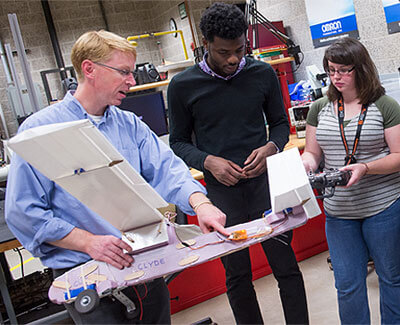 Brianno Coller (left) works with engineering students.