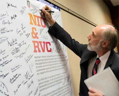 NIU President Doug Baker signs the declaration.