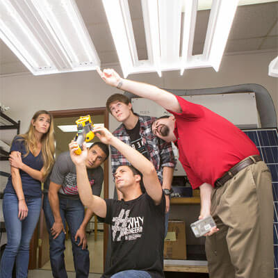 Professor Kevin Martin works with NIU students in the lighting lab.
