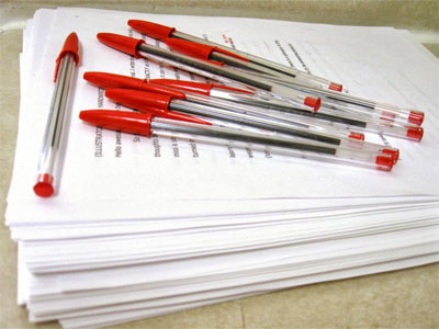 Photo of red pens on a stack of paper