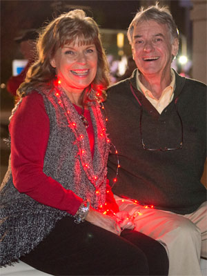Sue Corrao and fellow 1965 Homecoming Court member Dennis Twitty help NIU 'light the way' during the nighttime parade.