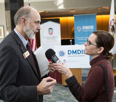 WNIJ reporter Jenna Dooley interviews NIU President Doug Baker at Monday's DMDII announcement.