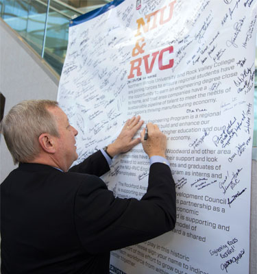 U.S. Sen. Dick Durbin signs his name to a banner celebrating the NIU-RVC Engineering Program.