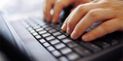 Photo of hands typing on a computer