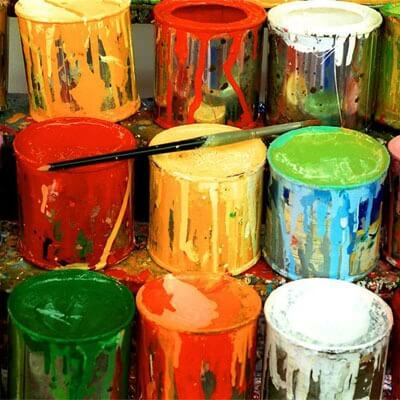 Photo of cans of paint and an artist's brush