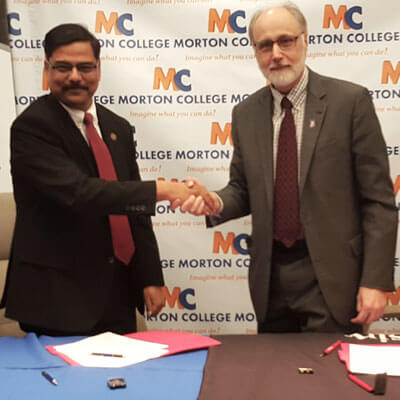 Morton College Interim President Muddassir Siddiqi (left) and NIU President Doug Baker shake hands after signing the reverse transfer agreement during a ceremony Tuesday at the Morton College campus in Cicero.