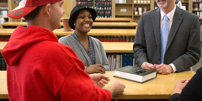 NIU College of Law students Neil Michling and Johnisha Sterling and Interim Dean Mark Cordes enjoy a light moment in the NIU Law Library.