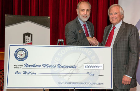 Robert Carr shakes hands with NIU President Doug Baker after announcing a $1 million gift from the Give Something Back Foundation to Northern for 50 Pell Grant-eligible students from Illinois high schools.