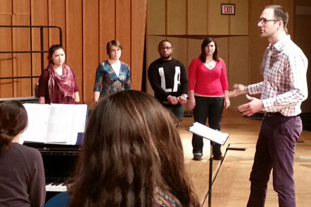 Timothy Takach leads a Thursday rehearsal on the stage of the Boutell Memorial Concert Hall.