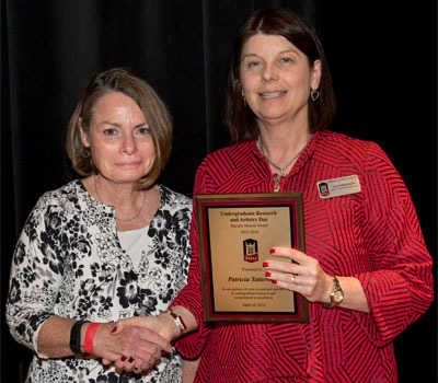 Patricia Tattersall (left) is congratulated by Lisa Freeman, NIU executive vice president and provost