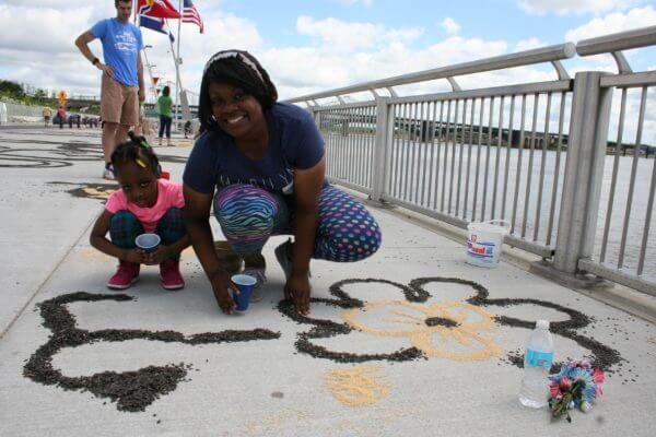Salina Govan of St. Louis and her daughter, Kristyahna Bradshaw, help decorate the Gateway Arch riverfront with birdseed art.