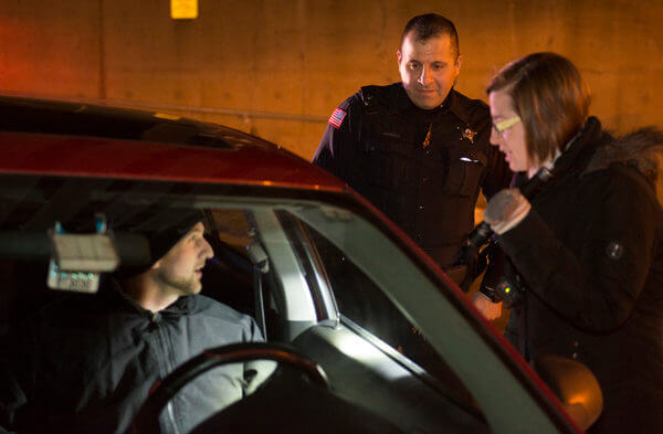 Director of Student Involvement and Leadership Development Jill Zambito learns what it's like to conduct a traffic stop with help from NIU Police Officer David Jadran during the 2016 Citizens Police Academy.